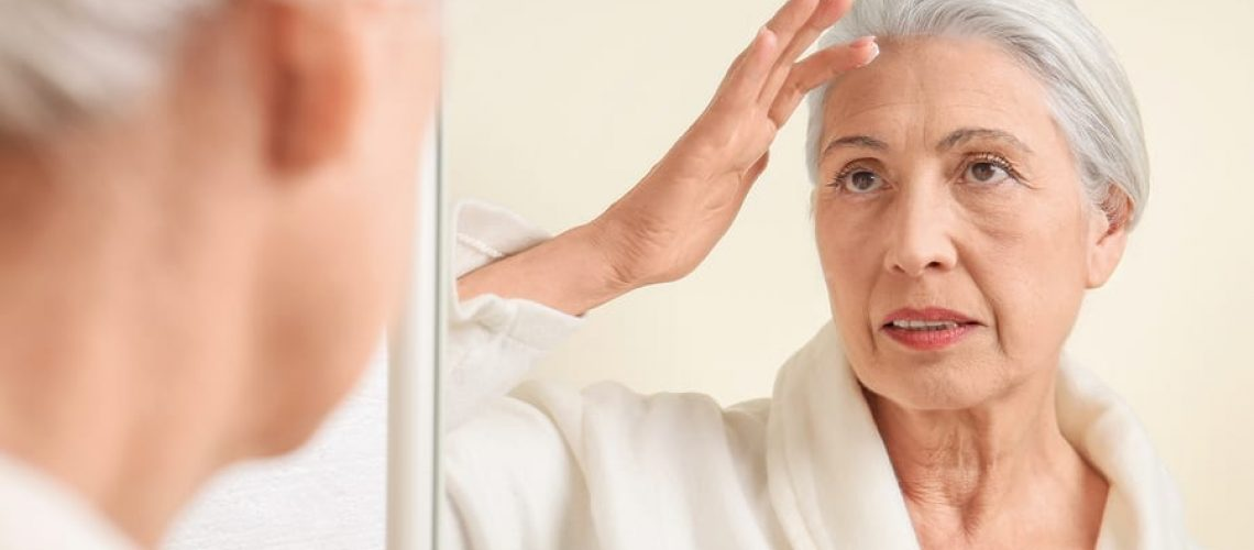 Beautiful elderly woman applying face cream in front of mirror at home